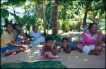 Group sitting on mats under trees