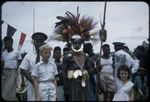 Highland native wearing bird of paradise plumes at Wabag, government appointed headmen wearing red banded caps in the background, between 1955 and 1960 / Tom Meigan
