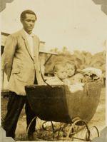 Tongan man with three children in one pram, 1928